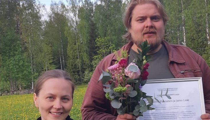 Lumilapio-palkinnon 2020 voittaneen Karoliina Paananen ja Jarno Liski kesäisessä maisemassa Lumilapio-palkinnon, kunniakirjan ja kukkien kanssa.